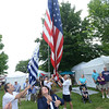 Newburyport: Yankee Homecoming General Chairman Tammy Jennings raises the Homecoming flag at the Mall Sunday. Jim Vaiknoras/staff photo