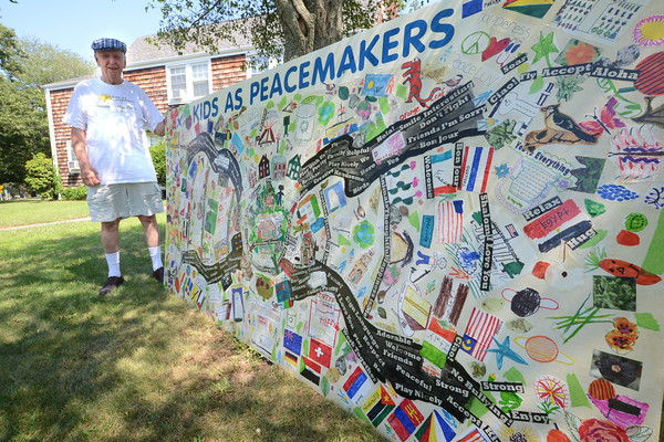 Newburyport: Merle Forney with one of the Kids as Peacemakers sign at Park Circle in Newburyport. Forney is moving to Pennsylvania. Jim Vaiknoras/staff photo