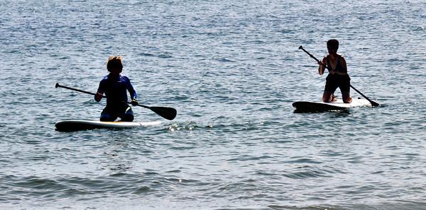 Salisbury: Two paddle boarders glide along Salisbury Beach Saturday morning. Jim Vaiknoras/staff photo