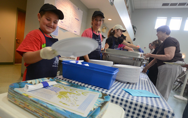 newburyport:Kostaki Tassis-Laskos, 7, hands out plates at the Greek Food Festival at Annunciation Church in Newburyport Friday. Jim Vaiknoras/staff photo