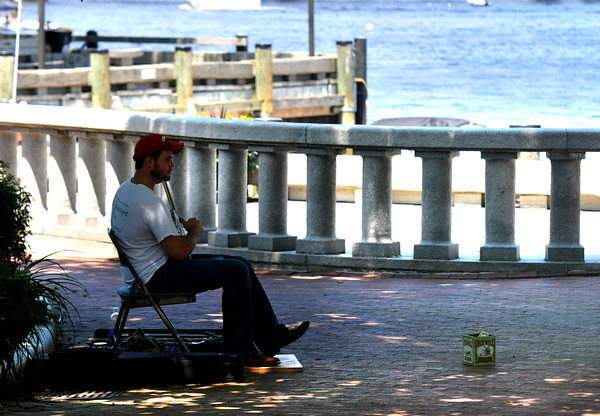 Newburyport: Nicholas Bogosian finds a bit of shade as he plays banjo in Market Landing Park in Newburyport Thursday  afternoon. Jim Vaiknoras/staff photo