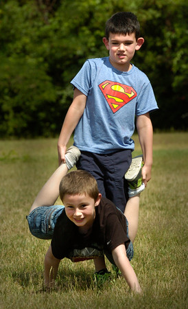 BRYAN EATON/Staff photo. Anthony Grasso, top and Robert Chernick, both 7, compete in the wheelbarrow race at the Boys and Girls Club on Monday. Water games are planned for later in the week as the temperatures will soar.