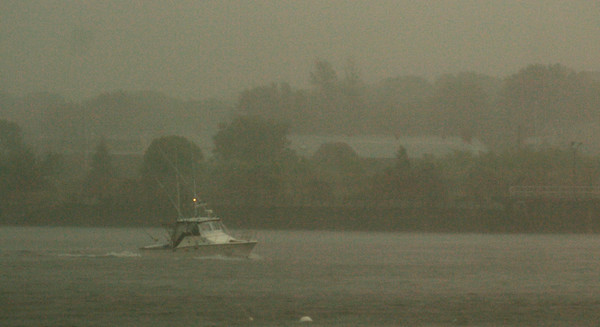 BRYAN EATON/Staff photo. A boater makes his way up the Merrimack River as the first wave of heavy rain and wind hit the area yesterday afternoon blurring the view  Newburyport waterfront. Nice weather is on tap for today and tomorrow.