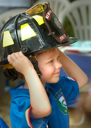 BRYAN EATON/Staff photo. Baker Harrison, 5, of Newbury tries on a firefighter's hat at the Emma Andrews Library on Thursday morning. The Newburyport Fire Department gave demonstrations to children and acquainted them with the equipment they use.
