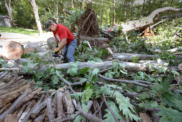 BRYAN EATON/Staff photo. Ben Lycnch cuts up a huge oak tree that was blown over and then toppled at the pine tree behind him on Birchmeadow Road. He does have a woodstove which he will use the wood for.