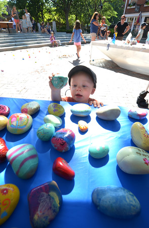 """JIM VAIKNORAS/Staff photo Oliver Egmont, 18 months, puts his decorated rock with other decorated rocks at Kindness Rocks! NBPT on Inn Street in Newburyport Wednesday. The event sponsered by Macaroni Kid had kids paint stones with hopefull messages like """"Believe to Dream"""", """"Joy"""", and """"Follow Your Heart""""."""