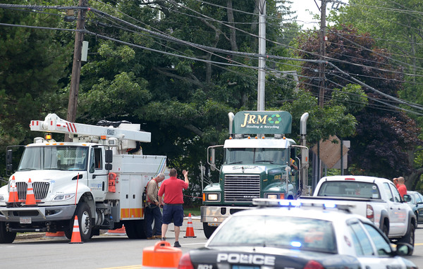 JIM VAIKNORAS/Staff photo workers guide a truck heading east under low hanging wires near the Dunkin Donuts on Story Ave in Newburyport Friday afternoon. Truck head west were turned around, causing heavy traffic.