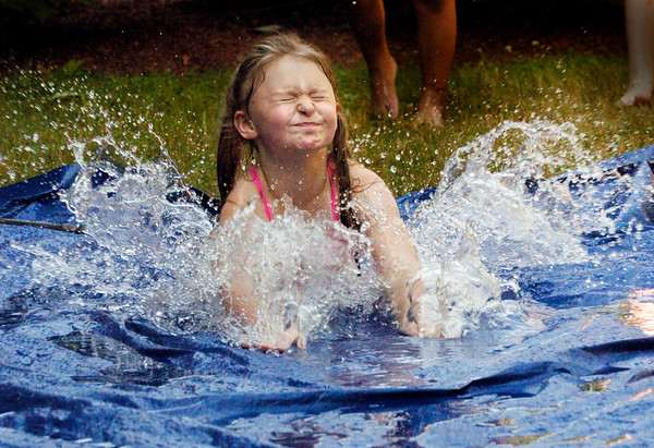 BRYAN EATON/Staff photo. Kaelee Smallidge, 8, of Salisbury cools off on a waterslide during Thursday afternoon's hot weather. She was at Summer Kid's Club at Salisbury Elementary School.