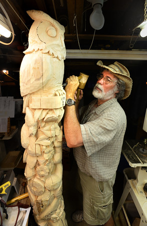 BRYAN EATON/Staff photo. Groveland artist Justin Gordon works on a totem pole in his workshop. Besides carving with chisel and hammer, he sculpts wood with a chainsaw and is also a sand sculpture.