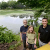 BRYAN EATON/Staff photo. Tom and Marlene Murphy, left, with Matt Healy are part of a group trying to rid Clarks Pond in Amesbury of an invasive water chestnut from Eurasia with the Latin name Trapa Natans. The edible seed is not the typical water chestnut found in Chinese cuisine.