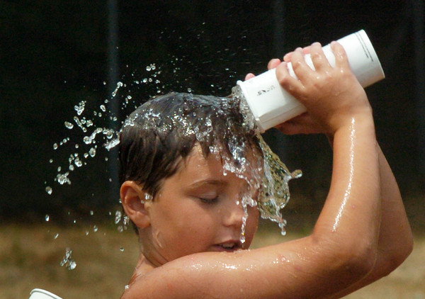 BRYAN EATON/Staff photo. Devin Menard, 9, of takes water from a relay game to douse himself with water during Monday's hot and muggy weather. The Newburyport boy was at the Boys and Girls Club.