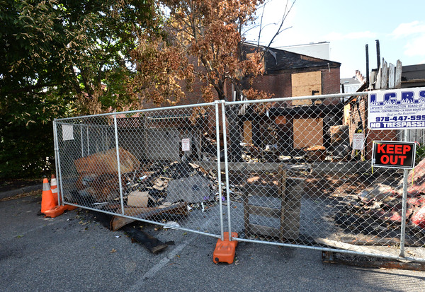 BRYAN EATON/Staff photo. Fencing still blocks the side of Abraham's Bagel Shop in Newburyport. A fundraiser is being held tonight for victims of the fire that damaged the businesses on Liberty Street.