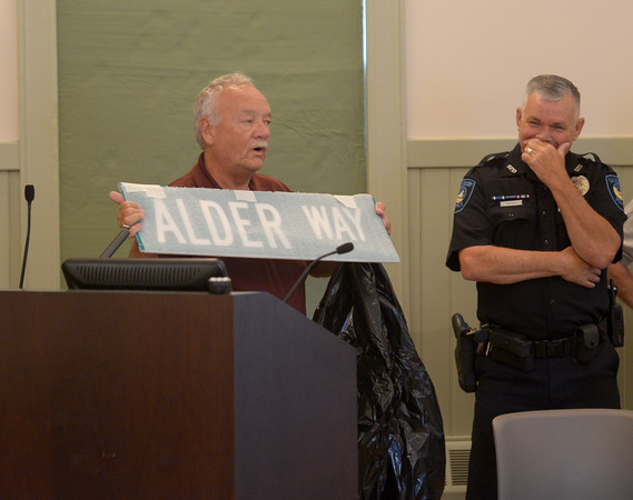 JIM VAIKNORAS/staff photo Head of the Salisbury DPW Don Levesque presents a street sign with his name on it, to retiring police officer Mike Alder at Town Hall Friday. Alder was hired as an auxillary officer, and as a full time officer in 1994.