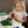 """BRYAN EATON/Staff photo. Elizabeth Kerr, 3, of Newburyport uses a pinecone as a paintbrush at a summer program at the Newburyport Montessori School. The theme of this week's camp is """"I Am Back and Explorer"""" the children finding items on a little hike and then creating art with them."""