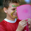 JIM VAIKNORAS/staff photo Joshua Banville , 10, seems to like the snake painted on his face by Renee Schneider during the Auction Under the Pines in Amesbury Monday. Proceeds from the event benifited the Bartlett Museum.