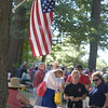 JIM VAIKNORAS/Staff photo People line up under the flag to buy tickets for   the annual Pancakes Under the Pines in Amesbury Monday.