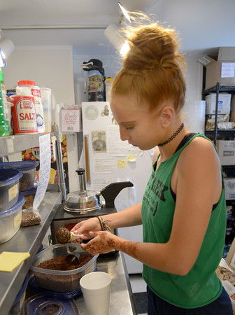 JIM VAIKNORAS/Staff photo Izzy Chesla puts sprinkles on a kiddie cone at Simply Sweet on Inn Street in Newburyport Thursday. Izzy resently graduated Newburyport high and will be attending Umass Amhearst this fall.