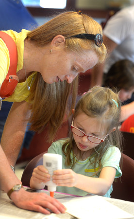 JIM VAIKNORAS/staff photo Scout Moyer ,4, gets some help from her mom Kate as she squirts glue on her salt painting at the Newburyport Library. salt paintings are made by pouring salt on wet glue, then dabbing the glue with water color paint creating a cool effect.