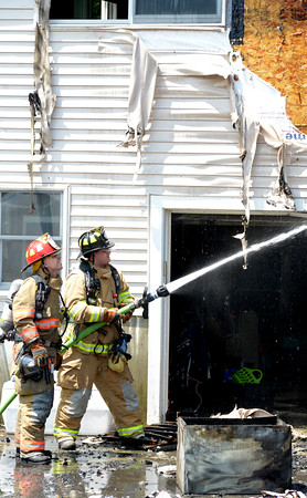 JIM VAIKNORAS/Staff photo Firefighters spray water on a fire on the back of a home  CCC road in Salisbury Sunday afternoon.