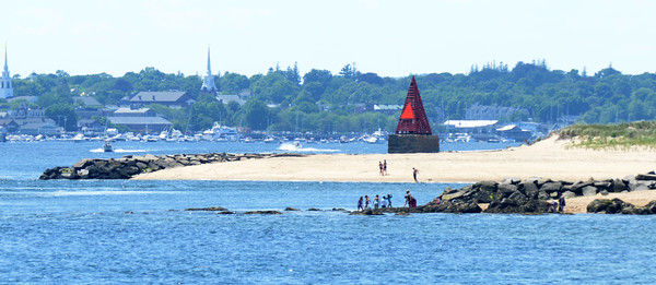 BRYAN EATON/Staff photo. Bathers plays on the rocks at Salisbury Beach State Reservation under the navigational aid Ben Butler's Toothpick on Thursday.