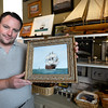 BRYAN EATON/Staff photo. The Custom House Maritime Museum is inviting artists to enter paintings of the ship El Galeon, which visited Newburyport in May, for an auction this fall, the proceeds of which will be split with the artists and the museum. Gift shop manager Jason Roberts shows off one of the first entries by Newburyport artist Herbert M. Crooks.