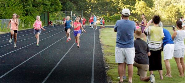 BRYAN EATON/Staff photo. Spectators photograph one heat of the girls 100 meter dash.