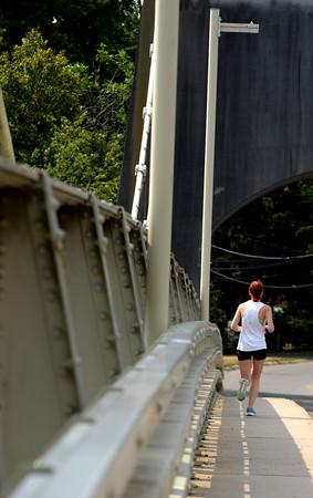 JIM VAIKNORAS/Staff photo A runner makes her way across the Chain Bridge connecting Amesbury to Newburyport Sunday morning.