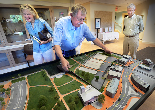 BRYAN EATON/Staff photo. Lon Hackmeister slides in a template of proposed redesign for parts of the Newburyport waterfront, after removing the present configuration in a 3-D model as Joan Purinton, left, and Nick Metcalf watch. The Committee for an Open Waterfront put forth a proposal, which in part, creates more green space in the NRA's East Lot.
