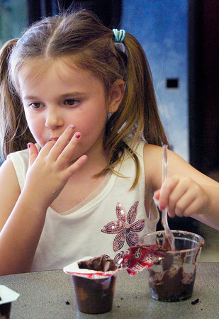 """BRYAN EATON/Staff photo. Lilly Stevens, 6, of Amesbury sneaks a taste of chocolate pudding at the Boys and Girls Club on Thursday. The younsgsters were making """"dirt"""" by pounding Oreo cookies, then mixing in the pudding and adding Gummy Worms."""