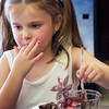 "BRYAN EATON/Staff photo. Lilly Stevens, 6, of Amesbury sneaks a taste of chocolate pudding at the Boys and Girls Club on Thursday. The younsgsters were making ""dirt"" by pounding Oreo cookies, then mixing in the pudding and adding Gummy Worms."