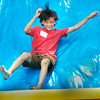 BRYAN EATON/Staff photo. Jonah Tarbell, 8, of Amesbury comes down the slide at the end of the bouncy obstacle course. He was at Amesbury Days' Kids Day in the Park.