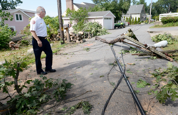 BRYAN EATON/Staff photo. Amesbury deputy fire chief Jim Nolan checks out the downed utility pole and lines on Birchmeadow Road where Monday's storm downed many trees, some onto homes.