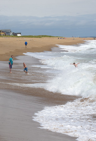 JIM VAIKNORAS/Staff photo Dispite Friday's cooler weather people enjoy swimming in surf on Plum Island. Unsettled weather is expected to move in this weekend.