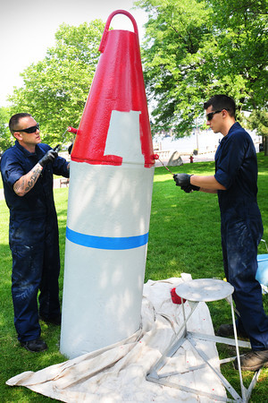 Newburyport: US Coast Guardsmen BM2 Justin Herring, left, and MK2 Joel Gyomory repaint the Nun Boy at Newburyport's Waterfront Park. The buoy was presented to the city by the US Coast Guard in 1962 and these two from from the Boston station Aids to Navigation Team volunteered their time to refurbish the buoy. Bryan Eaton/Staff Photo