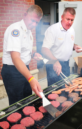 Amesbury: Firefighters know where there's smoke, there's fire, especially Amesbury fire Chief Jonathan Brickett, left, and deputy chief David Mather. The two were cooking hot dogs and hamburgers, where the wind was blowing in the wrong direction, at the Amesbury Days Annual Senior Citizens Cookout yesterday afternoon. Bryan Eaton/Staff Photo