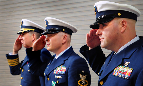 Newburyport: US Coast Guardsmen salute at the removing of the flags at a change of command ceremony at Station Merrimack River yesterday in Newburyport. From left, Capt. John C. O'Connor III; Jason B. Holm, retiring officer in charge of the station and his replacement Mark W. DiLenge. Bryan Eaton/Staff Photo