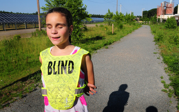 Salisbury: Shauna Roaf, a blind 10-year-old Amesbury Elementary School student will be running along the Salisbury Point Ghost Trail, behind, in the Adaptive Athletes category of the Pat Polletta Road Race tonight. Bryan Eaton/Staff Photo