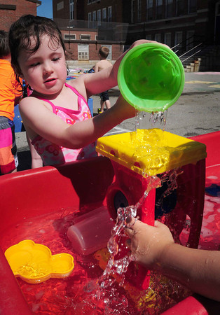 Newburyport: Audrey Gavin, 4, pours water into a toy at the Brown School on Monday. The pre-kindergarten classes were having a Water Day to cool down. Bryan Eaton/Staff Photo