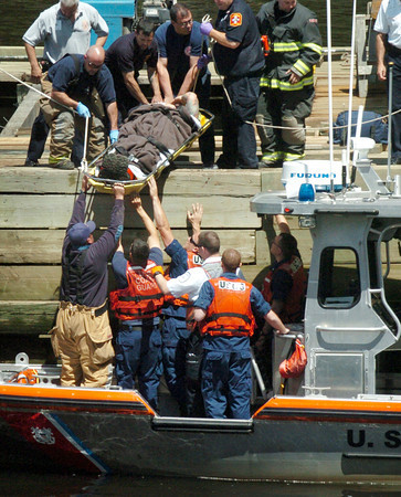 Amesbury: Amesbury and Newburyport Fire and Rescue crews lower a an worker to an awaiting US Coast Guard craft on the pier of the Hines Bridge yesterday morning.  The man, suffering trauma to the head was airlifted to a Boston hospital. Bryan Eaton/Staff Photo