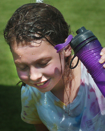 Amesbury: Hannah Balaam, 9, drizzles cold water over her head taking a break from Field Days at Amesbury Elementary School. The hot temperatures are expected to continue all week with spot storms possible. Bryan Eaton/Staff Photo