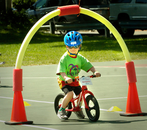 BRYAN EATON/ Staff Photo. Benjamin Marchand, 3, of Newburyport rides through the obstacle course on the tennis courts at Cashman Park in Newburyport on Sunday morning. He was participating in the Greater Newburyport Pan-Mass Challenge Kids Ride to raise money for the Dana Farber Cancer Institute's Jimmy Fund.