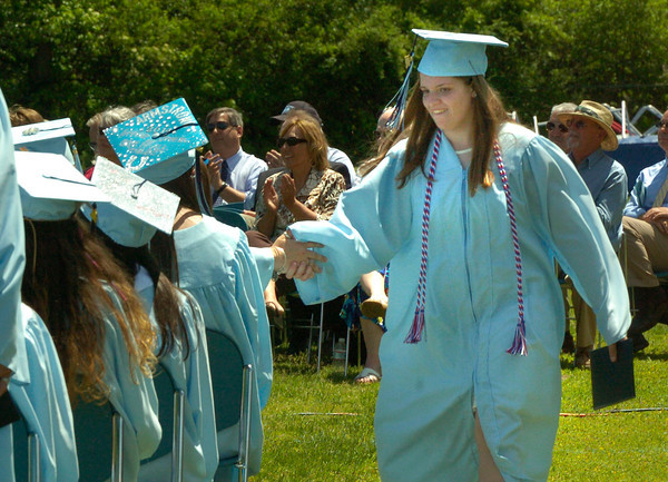 BRYAN EATON/ Staff Photo. Sydney Marino gets a handshake from a classmate after getting her diploma.