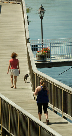 BRYAN EATON/ Staff Photo. Joggers, dog walkers and bicyclists were in abundance Monday afternoon on the Harborwalk near Cashman Park. The nice weather stays another day with showers likely Wednesday and Thursday with clearing for the weekend.