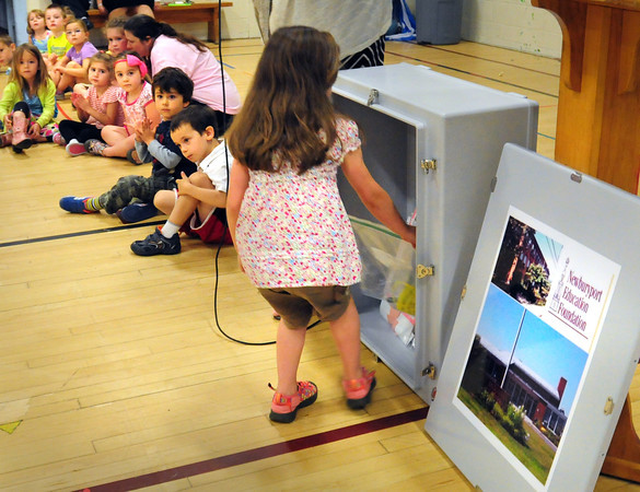 BRYAN EATON/ Staff Photo. Riley Lombard, 6, puts in items in the time capsule at the Brown School for Tracy McLaughlin's kindergarten class.