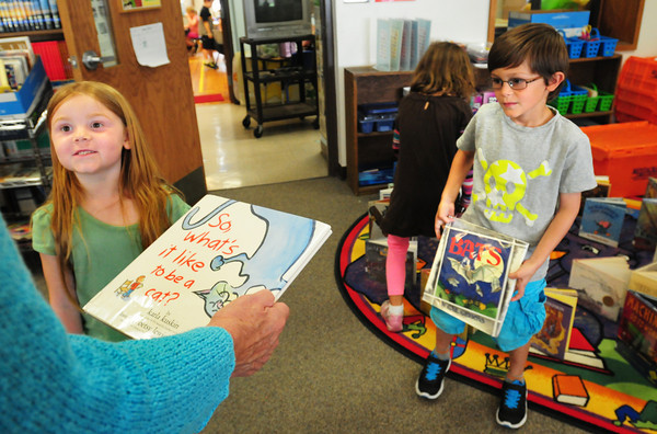 BRYAN EATON/ Staff Photo. The Brown School in Newburyport, which closes for good today, let each student take home two books from the library as momentos of their time there. Bree Thresher, 5, left shows one book to assistant Mary Todd as Charlie Field, 6, has his book in hand.