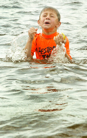 BRYAN EATON/ Staff Photo. Maxx Rodrigues, 6, of Amesbury jumps out of the choppy water caused by the strong wind at Lake Gardner Beach yesterday afternoon. Though the temperature approached 90 degrees, the wind made it seem cooler.