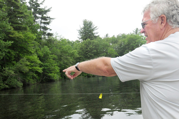 BRYAN EATON/ Staff Photo. Lake Attitash resident Jack Sanborn points to the invasive water weed Milfoil in Turtle Cove. A line is set up to keep boats from churning the weeds up allowing them to float to other parts of the lake to take root.