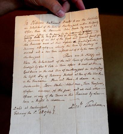 BRYAN EATON/ Staff Photo. Scott Nason shows the document dated February 1, 1764 which seperated Newburyport from Newbury.