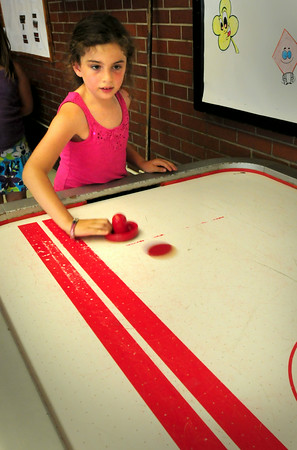 BRYAN EATON/ Staff Photo. Sheayla Capuci, 8, plays a game of air hockey at the Boys and Girls Club in Salisbury, though air blowing out of the holes was hardly enough to cool one down.