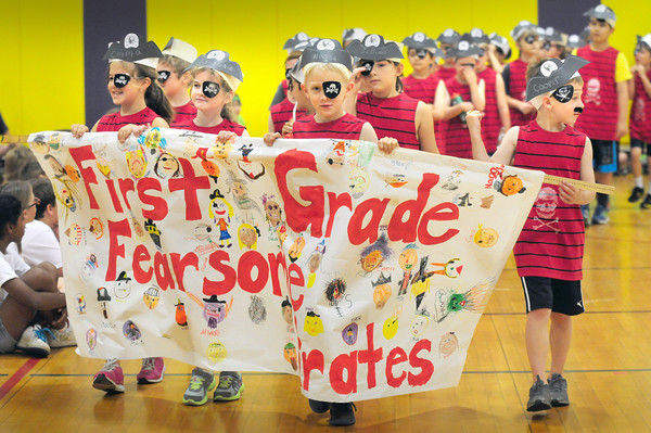BRYAN EATON/ Staff Photo. The First Grade Fearsome Pirates parade into the gymnasium at Newbury Elementary School on Tuesday. Each class had a different theme and dressed the part along with the banner as they started their Field Day activities.